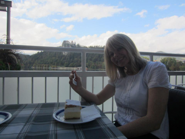 Kat munching a kremsnita with Bled castle in the background