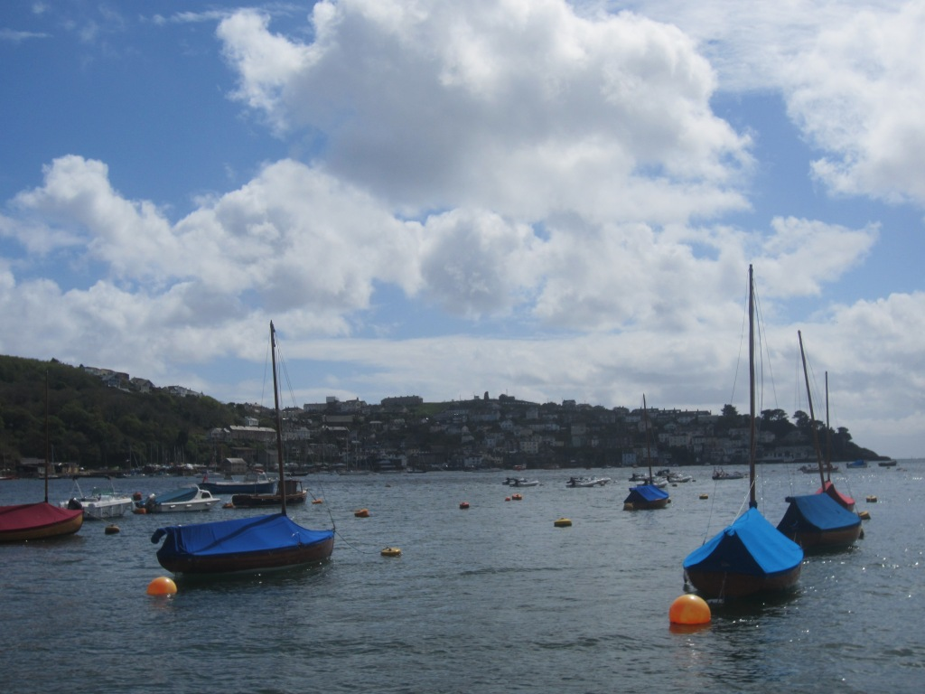 Covered fishing boats bob in the water between Fowey and Polruan.